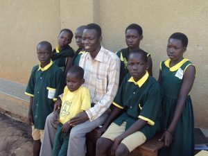 Pupils take photo with director on arrival at Fountain Primary School